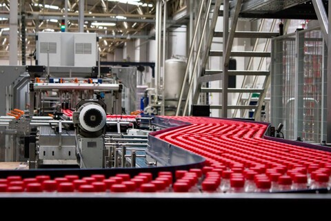 A factory line full of red-capped bottles.