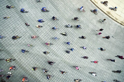 Top down view of people riding bikes in a plaza.