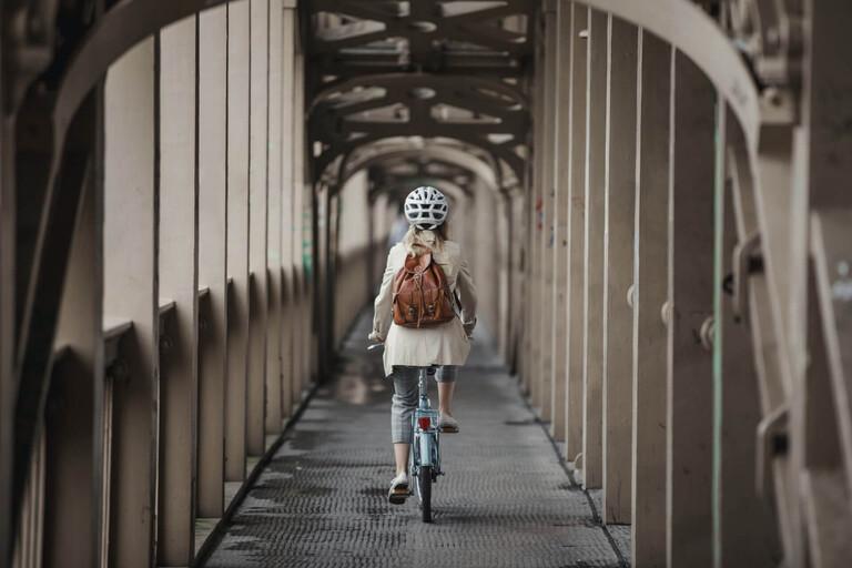 Rear shot of a woman riding a bicycle down a bridge's bike path.