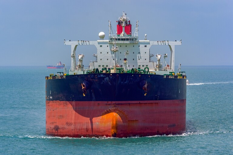 A large red/navy oil tanker's bow.