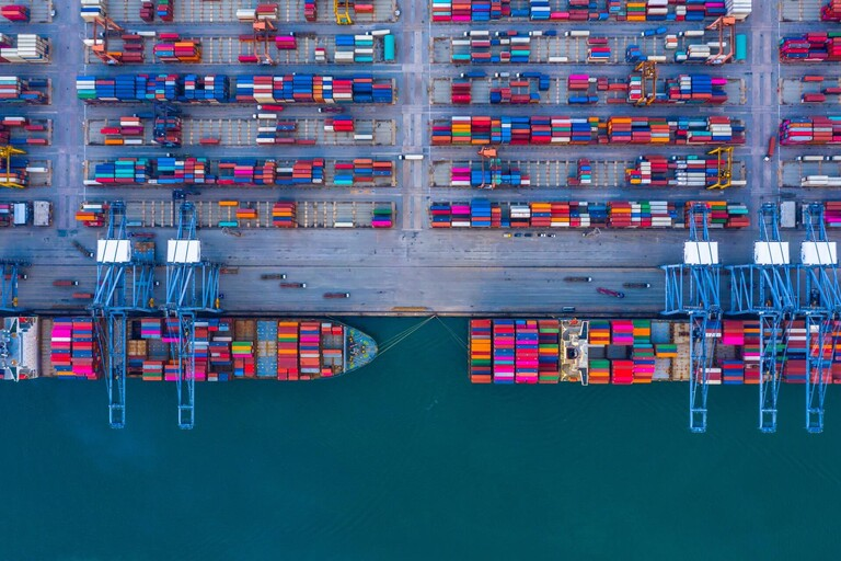 Aerial shot of docked cargo ships being loaded.