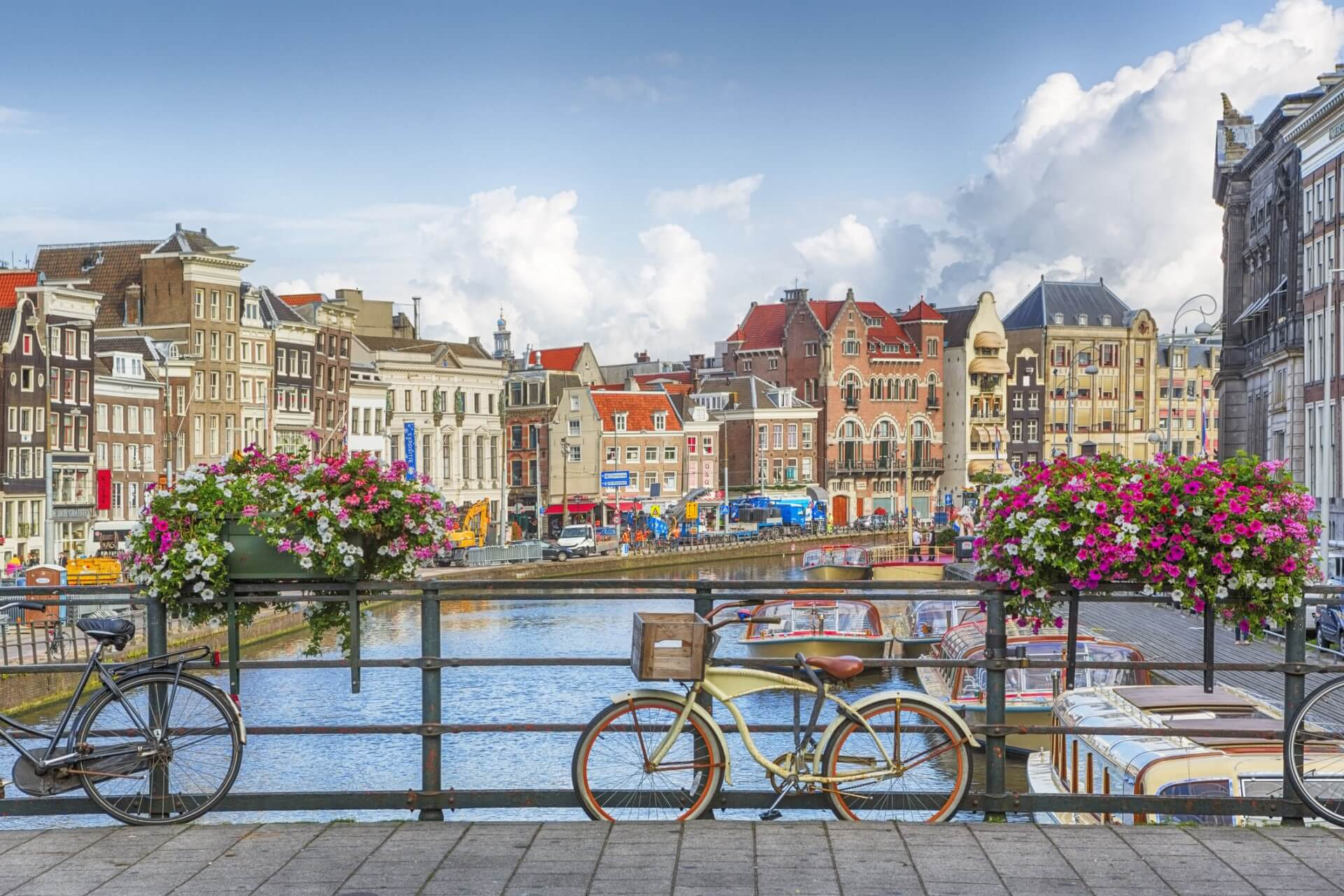 Bikes on a bridge over a canal, potted flowers on the railings.