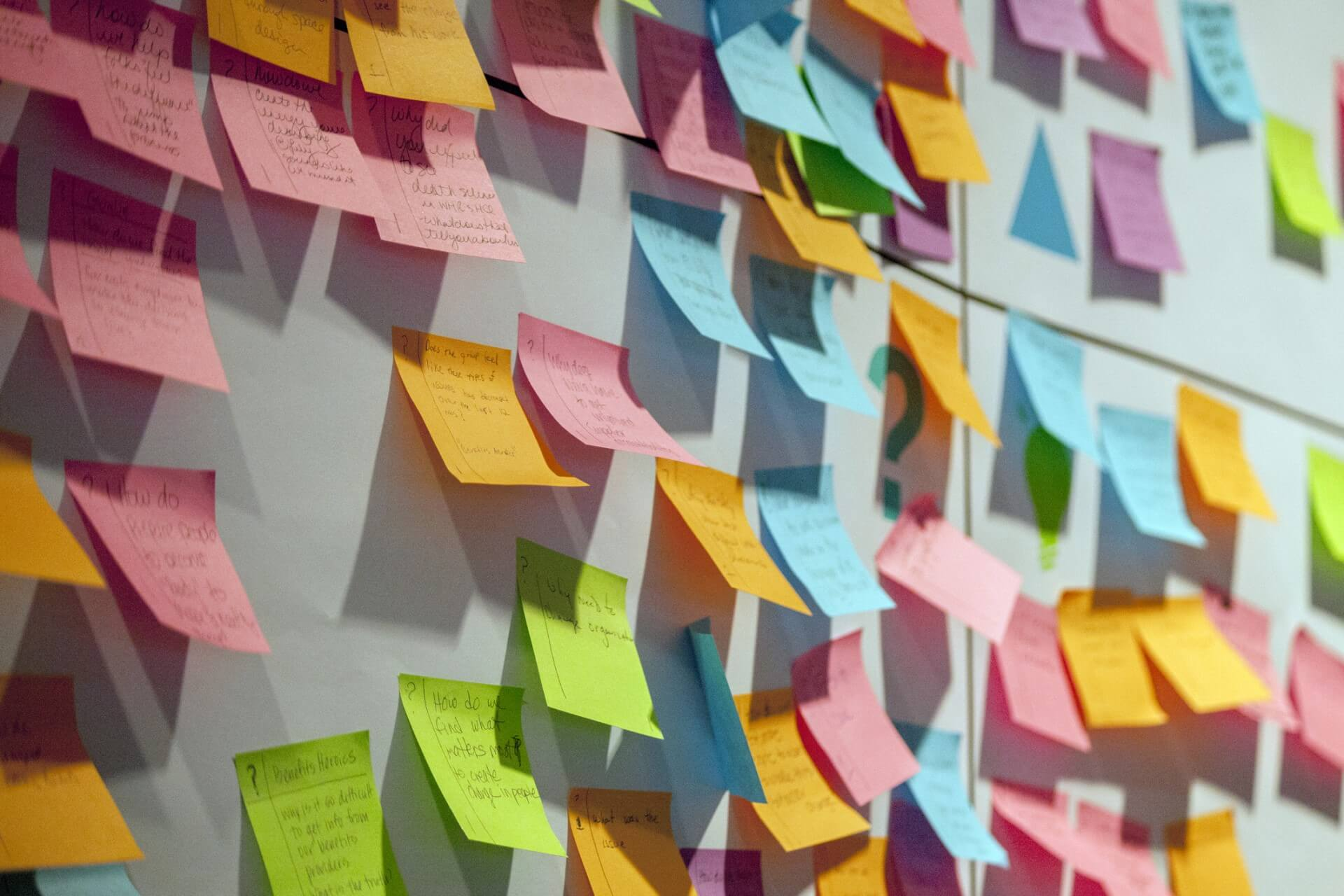 Multi-color sticky notes posted onto a wall.